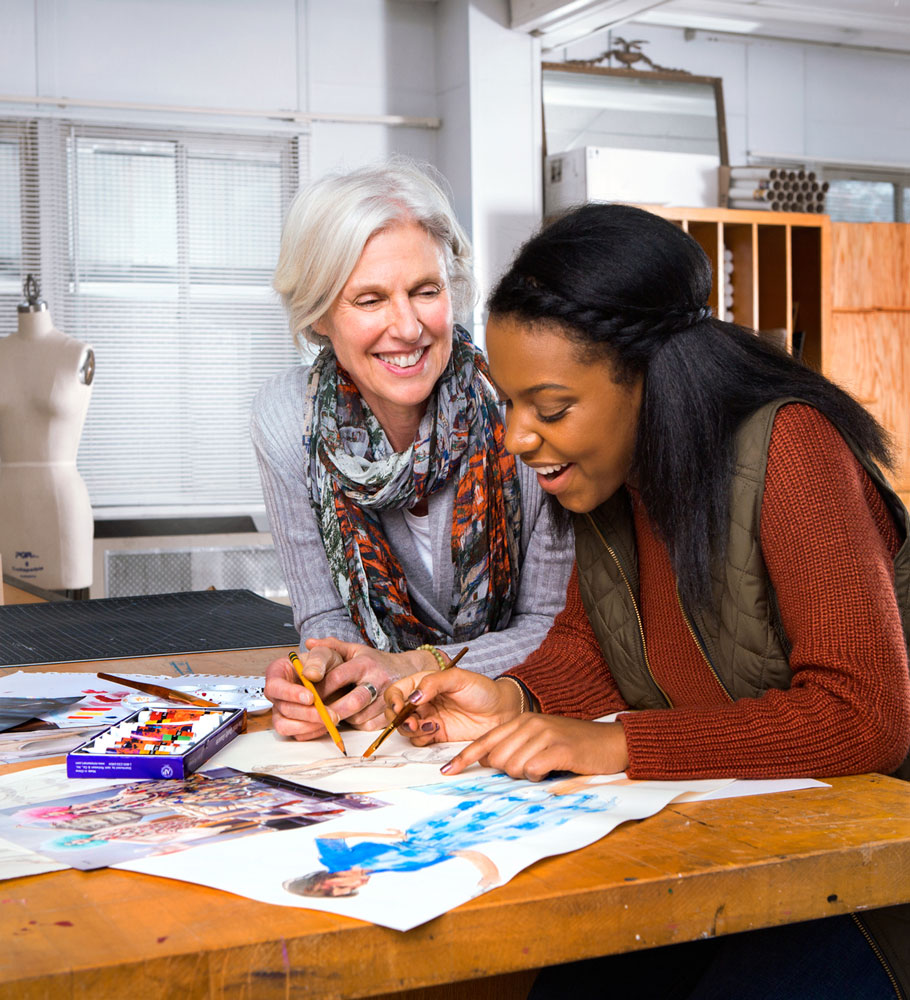 Woman drawing while other woman smiles and watches